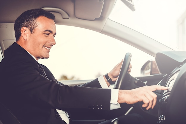 Вождение с комфортом. вид сбоку веселого зрелого мужчины в формальной одежде за рулем автомобиля и касания пальцем приборной панели