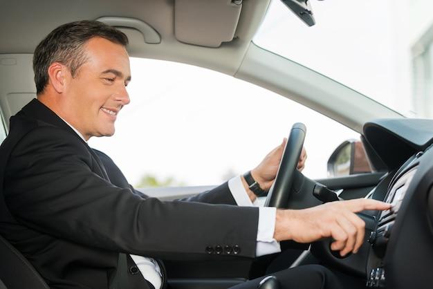 편안한 운전. 차를 운전하고 손가락으로 대시보드를 만지는 포멀웨어를 입은 쾌활한 성숙한 남자의 측면 보기