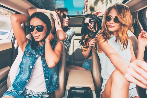 친구들과의 드라이브는 언제나 즐겁습니다! 행복하고 쾌활해 보이는 4명의 아름다운 젊은 쾌활한 여성