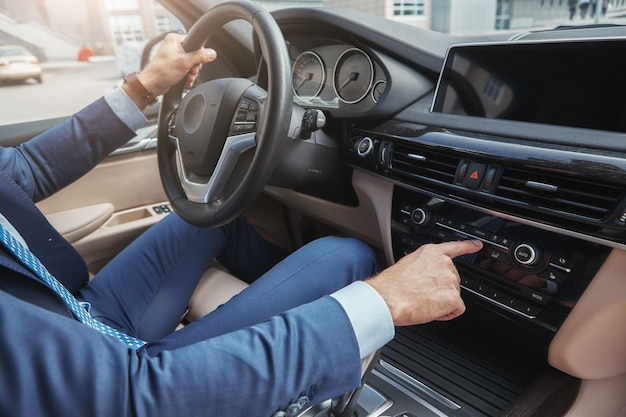 Driving with music cropped image of businessman in formal wear pushing buttons of music player