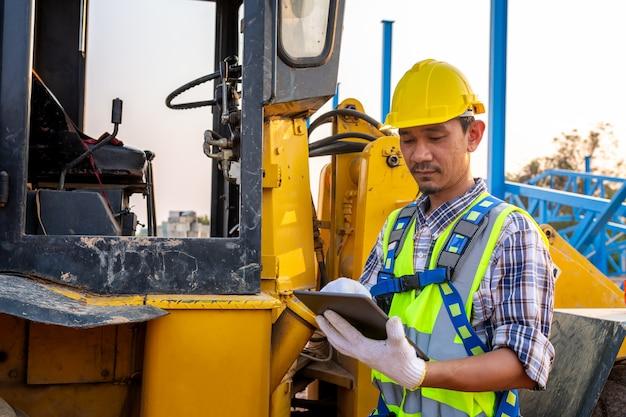 Вождение рабочего тяжелого колесного трактора, рабочие ведут заказы через планшет, колесный погрузчик экскаватор с экскаватором, разгрузкой песка, работает на строительной площадке.