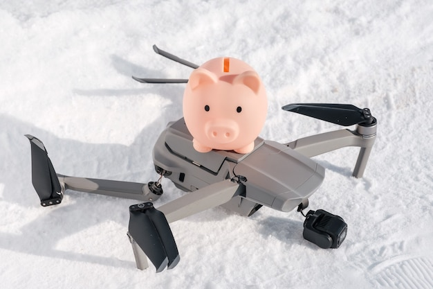 Drone after crash and piggy bank on snow