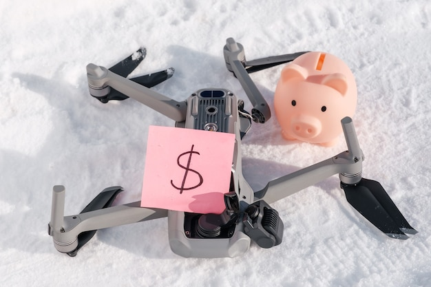 Drone after crash, sticky note with dollar sign and piggy bank on snow