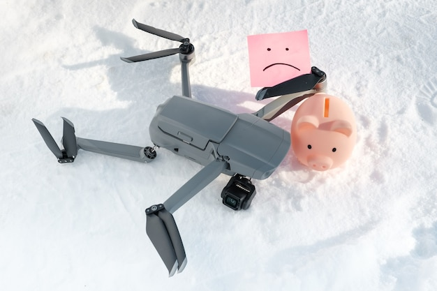 Drone after crash, sticky note with sad smile and piggy bank on snow