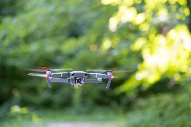 ぼやけた高速回転プロペラと空を飛ぶフォトカメラを備えたドローン航空機。
