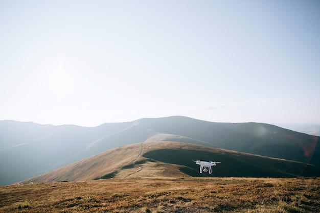 山でデジタルカメラで飛んでいるドローンヘリコプター