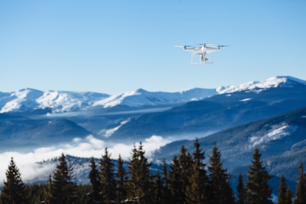 Drone copter flying with digital camera over the mountains