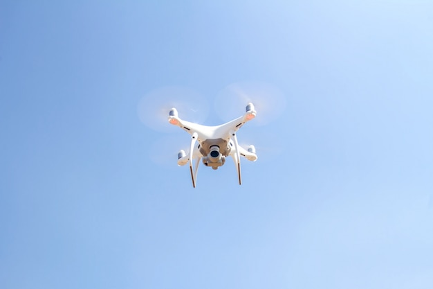 Drone copter flying with digital camera on the sky and sunlight