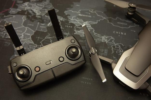 世界地図背景にリモートコントローラーとドローンヘリコプター