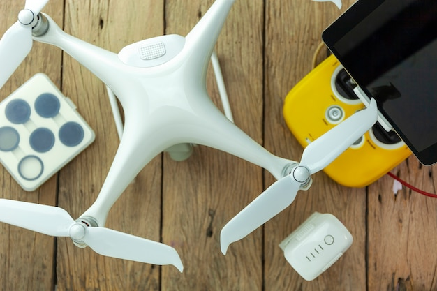 Drone equipment with remote control on wood background