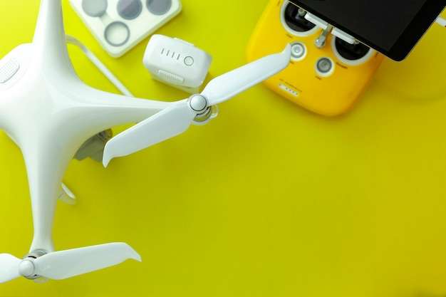 Drone equipment with remote control on yellow paper background, copy space for your text top view image