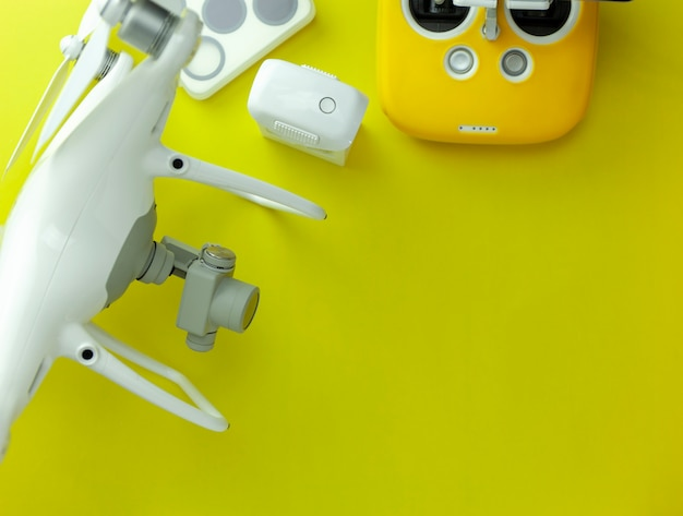Drone equipment with remote control on yellow paper background