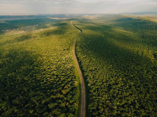 여름 화창한 날 공중에서 내려다보이는 일몰 고속도로 여행에서 푸르고 장엄한 숲을 가로지르는 아스팔트 도로 위의 드론 비행