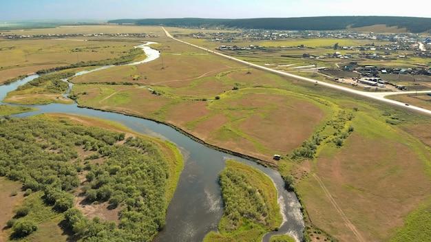 ドローンは、地上道路、空撮風景と森や野原に囲まれたカーブした川の上を飛ぶ