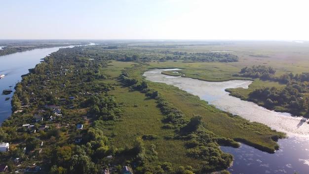 무인 항공기는 다양한 건물이있는 지역 마을로 둘러싸인 푸른 색의 강을 날아갑니다.