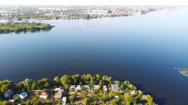 드론은 지역 마을에 둘러싸인 푸른 색의 강을 흔드는 비행