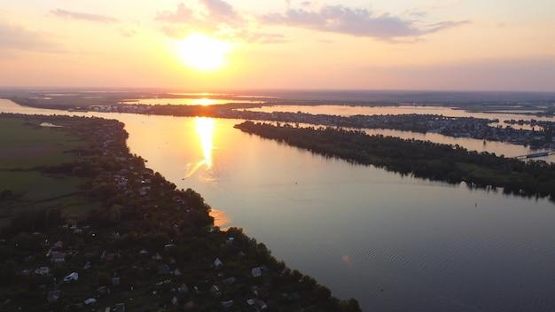 다양한 건물과 습지가있는 지역 마을로 둘러싸인 물결 치는 강 위로 드론 비행