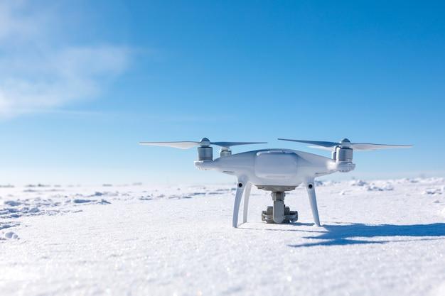 晴れた冬の日に雪に覆われたフィールドの上を飛んでいるドローン