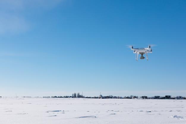 Дрон летит над полем, покрытым снегом, в солнечный зимний день