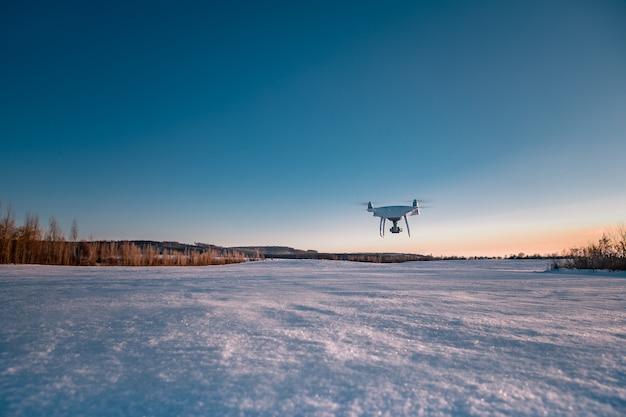맑은 겨울 날에 눈으로 덮여 필드 위에 비행하는 무인 항공기