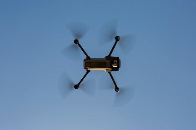 Drone flying against a blue sky