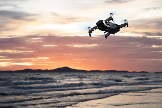 Drone flying against the mountain and sea or ocean at sunset sky.