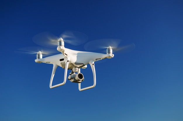 Drone flying over the blue sky background