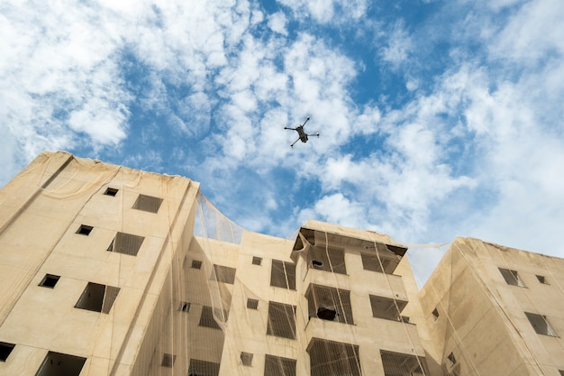 A drone flying next to building under construction.