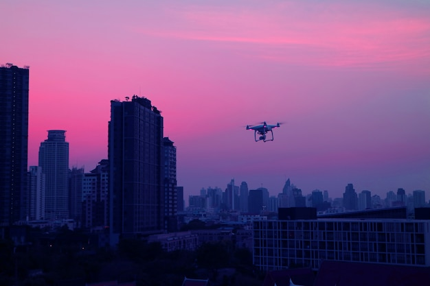 Drone flying in evening sky over the skyscrapers of bangkok's suburban, thailand