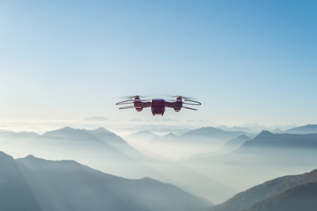Drone flying over foggy and snowy high hills and mountains