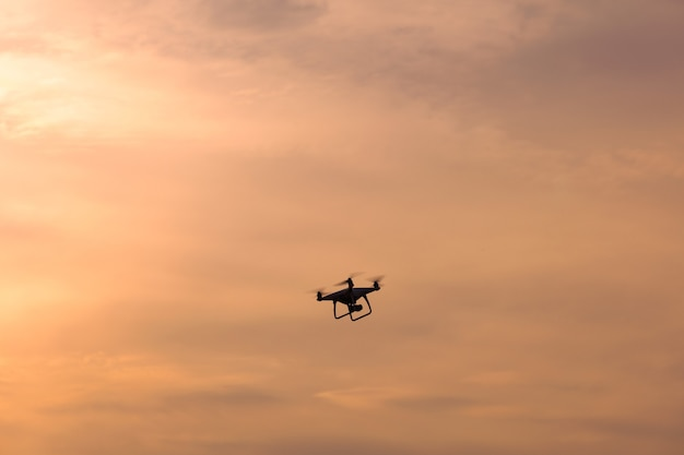 Дрон, летящий в небе на восходе солнца