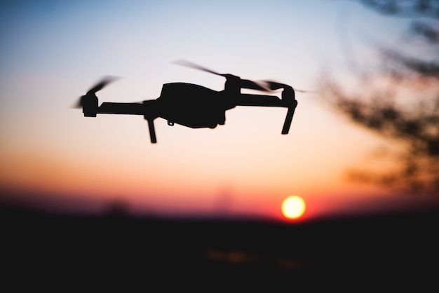 夕日に飛んでいるドローン。カラフルな空を背景にドローンのシルエット。