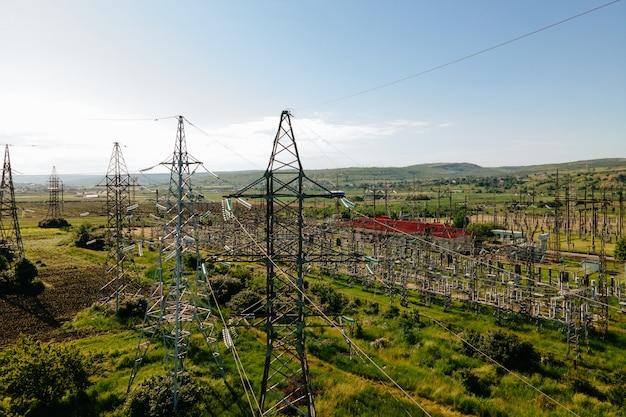 농경지 위를 날고 있는 드론과 아름다운 하늘 농부를 향한 고압 전기 철탑...