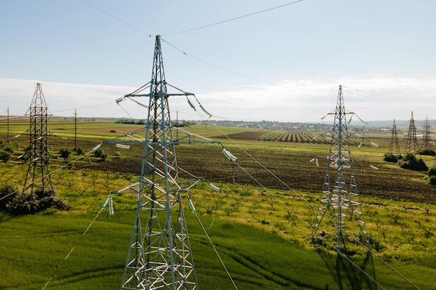 아름다운 하늘 농부의 비옥한 들판 농업과 에너지 개념에 대항하여 농경지와 전기 고전압 철탑 위를 나는 드론