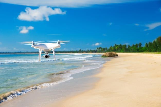 海の上を飛んでいるドローン。真っ青な空に浮かぶ白いドローン。空中写真撮影の新技術。