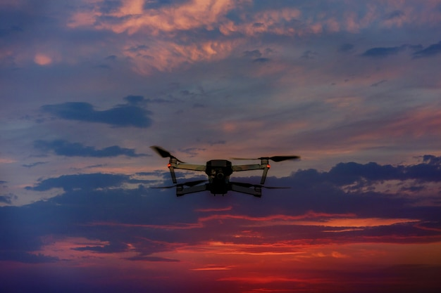 Drone flying over a sunset sky with light clouds