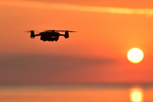 Drone flying in the sunset sky .