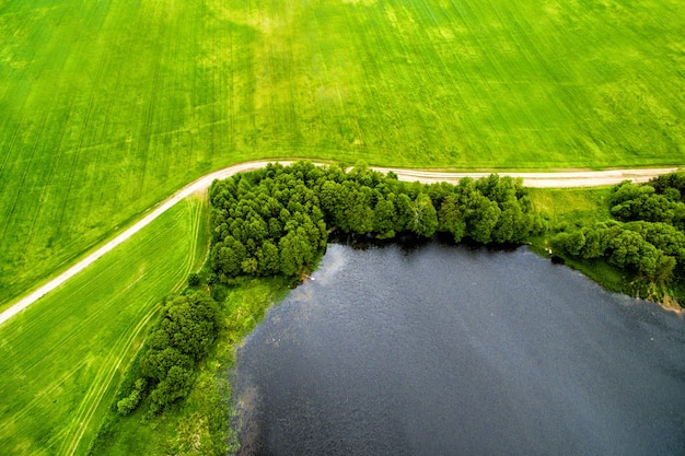 田舎の自然の湖の道と牧草地のドローン画像