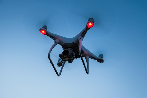 Drone is flying in the blue sky at sunset time. modern technological background - silhouette of flying machine