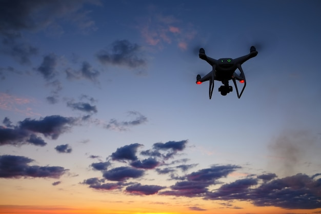 Drone is flying over the field at sunrise. modern technological background - silhouette of flying machine in glowing red sunset sky.