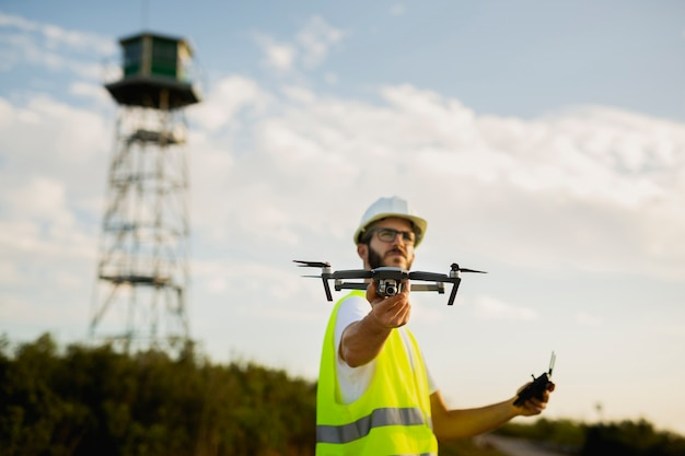 Drone operator launching a drone on a countryside environment