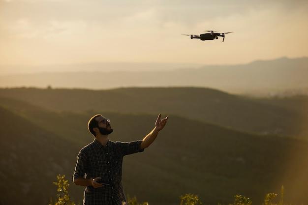 田舎の設定でドローンを操縦するドローンオペレーター