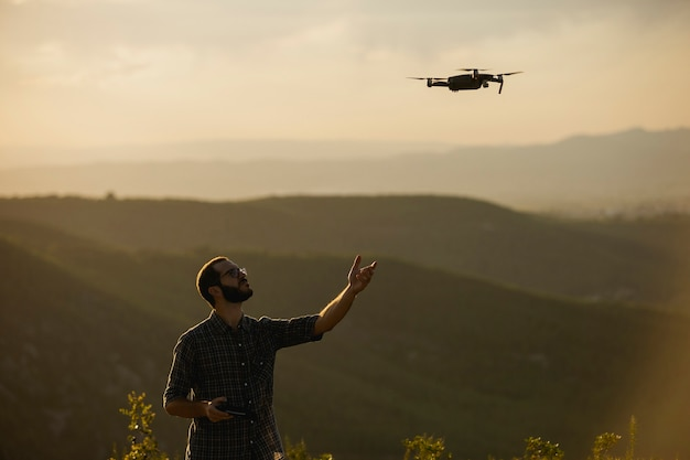 Drone operator piloting a drone in a rural setting