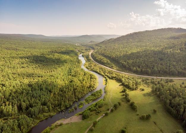 강, 시골 길 및 숲을 통해 무인 비행기. 시냇물, 침엽수 림 및 언덕의 공중 놀라운 전망. 화창한 날에 최고의 자연 풍경입니다. 물