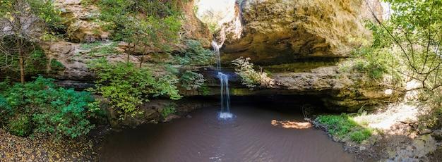 Панорама с дрона на водопад в цыпово, молдова. пещера и зелень