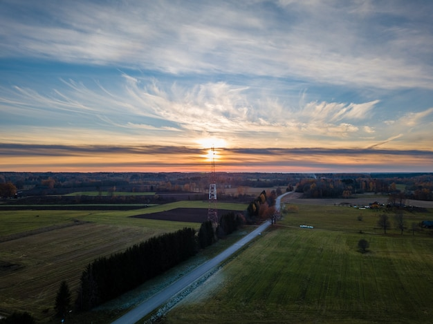 Drone photo of empty road leading through the rural village - colorful autumn sunset