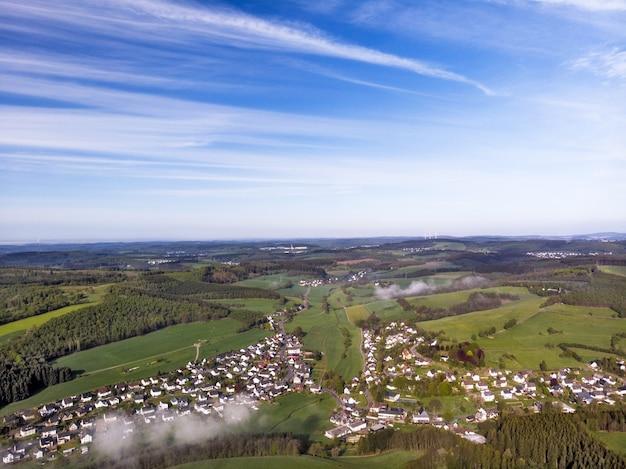 晴れた日の田園地帯の美しい緑の野原のドローン写真