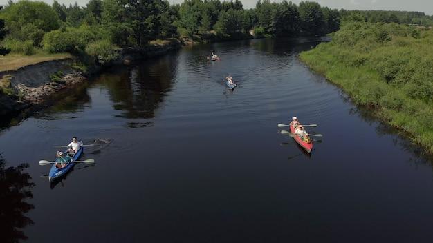 水に浮かぶグループの人々のカヤッカーのドローンの視点。湖のグループカヤックの空中ドローンビュー。川床の空中写真に沿ったカヤックとカヌー。ラフティング。ボートの追跡