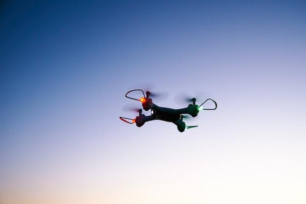 夕焼け空を背景にドローンクワッドコプターのおもちゃ
