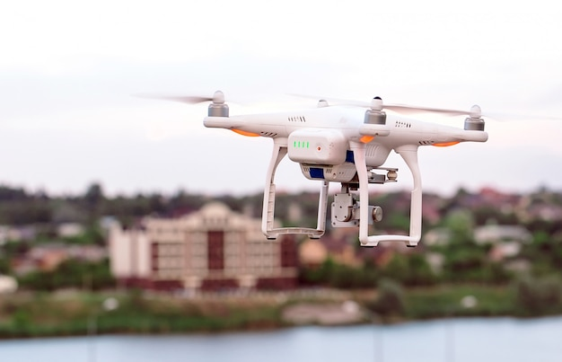 Drone quad copter with high resolution digital camera flying hovering over the city